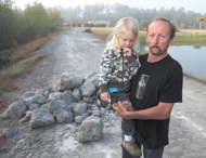Steve Johnson and his daughter with coal ash product at their home.