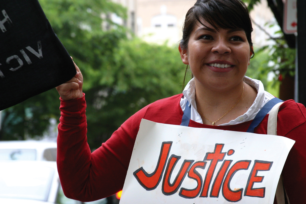 A young woman holding a sign that says justice