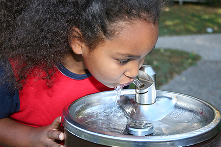 Young girl drinking from a water fountain