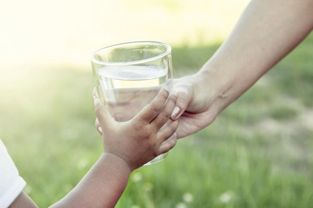 Handing a glass of water to a child. Photo credit: iStock