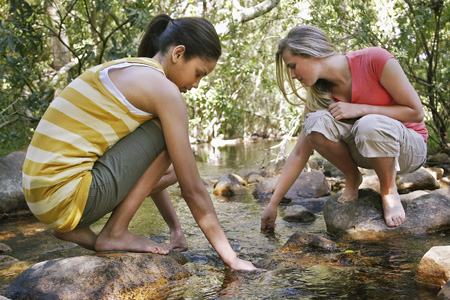 Young women on a creek. Photo credit: iStock