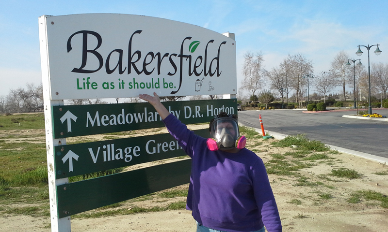 Rosanna in a respirator in front of a Bakersfield's sign