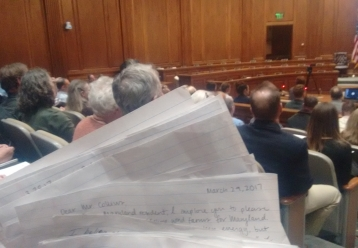 The public hearing room, full, with handwritten letters held in the foreground