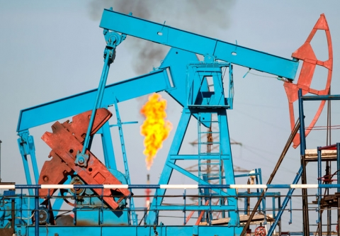 Pumpjacks with a methane flare in the background. Photo credit: Leonid Ikan / Shutterstock