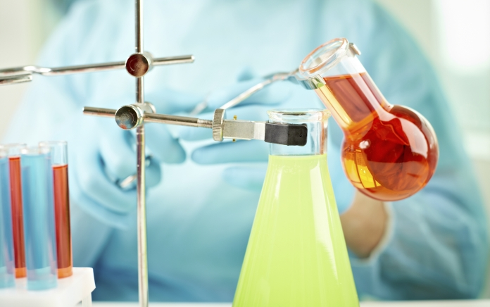 Chemicals being mixed in beakers. Photo credit: mediaphotos / Shutterstock