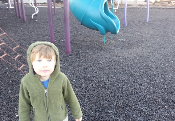 A child at a playground using waste tire mulch