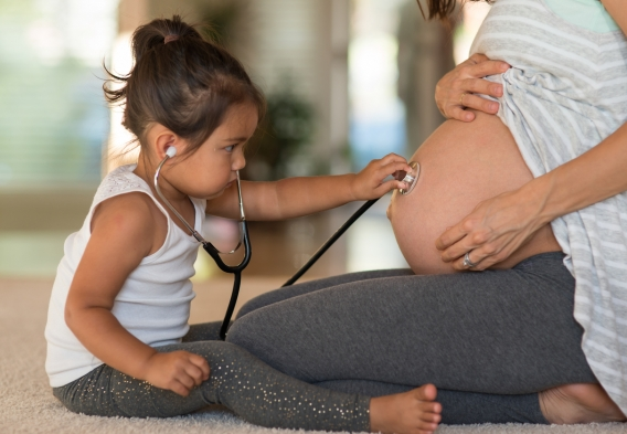 toddler with stethoscope listening to pregnant belly. photo: istock