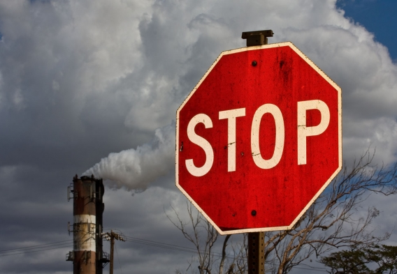 Smokestack and stop sign. Photo credit: Shawn Hempel / Shutterstock
